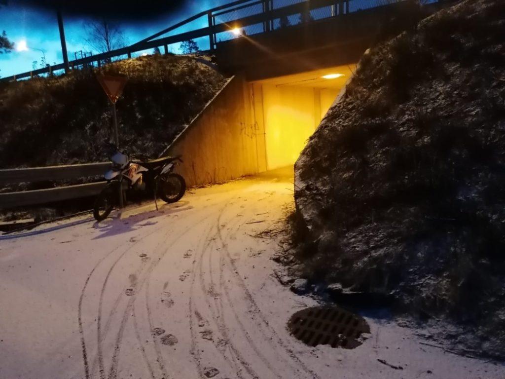 Kuvassa tunneli, talvinen ympäristö, kuvan keskellä on mopo, maassa lumessa pyörän jälkiä