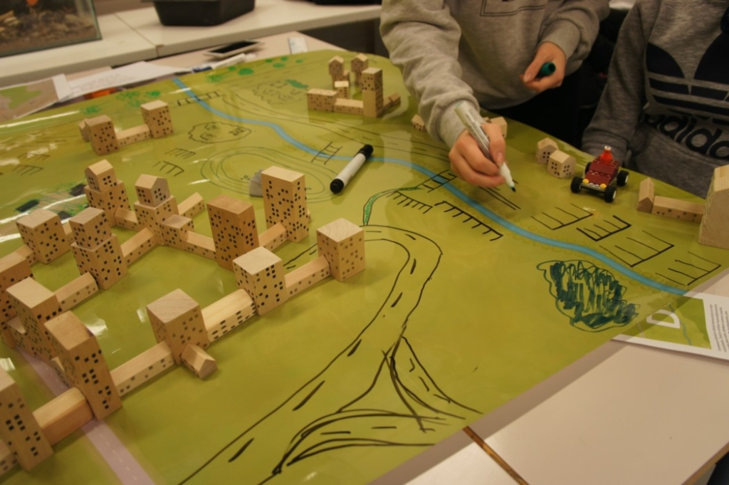 Kuvassa on pulpetti, jonka päällä on kartta. Kartassa on palikoista rakennettua kaupunkia. Kuvassa käsi joka piirtää kartalle teitä.