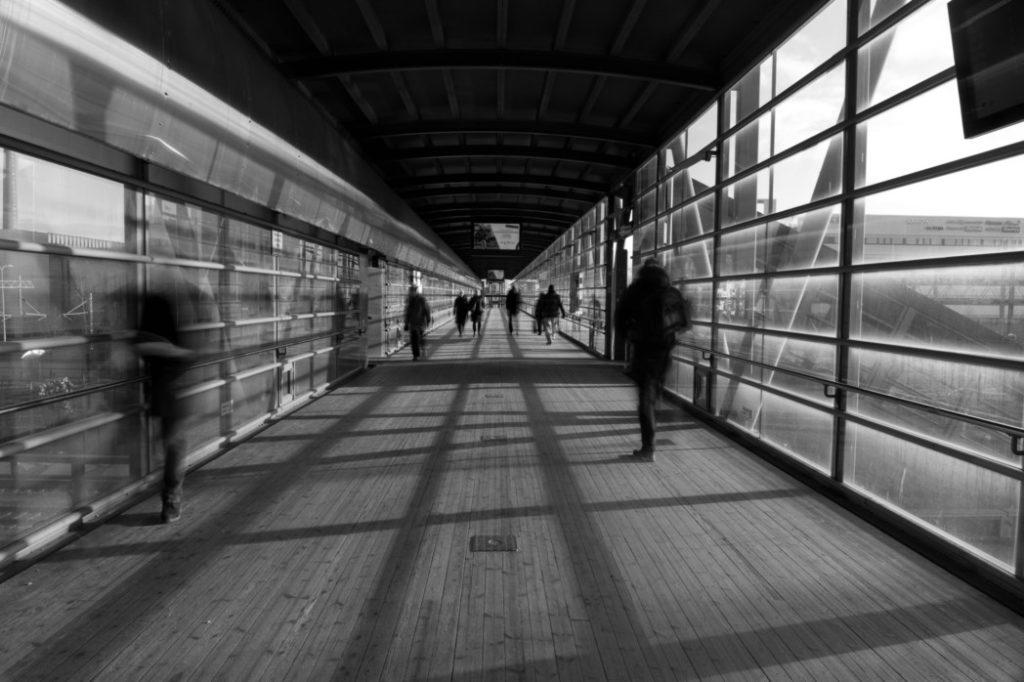 ylikulkusilta, jossa ihmishahmoja kulkee, kuva on mustavalkoinen ja hahmot liikkeessä