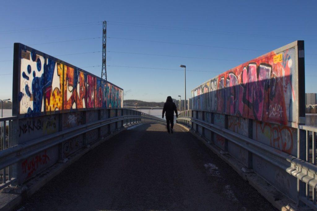 ihminen kävelee sillalla, silta on maalattu värikkäillä graffiteilla, taivas on sininen, talvi