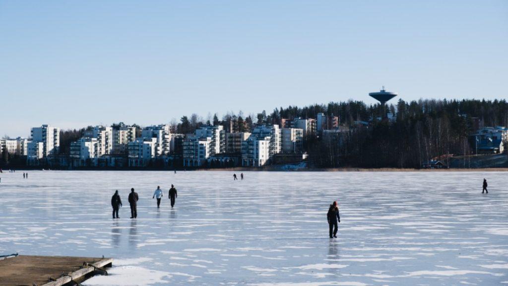 talvinen järvimaisema, ihmisä jäällä, sininen taivas, taustalla näkyy kaupunkimaisemaa