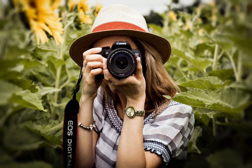 nainen kuvaa kameralla katsojaa