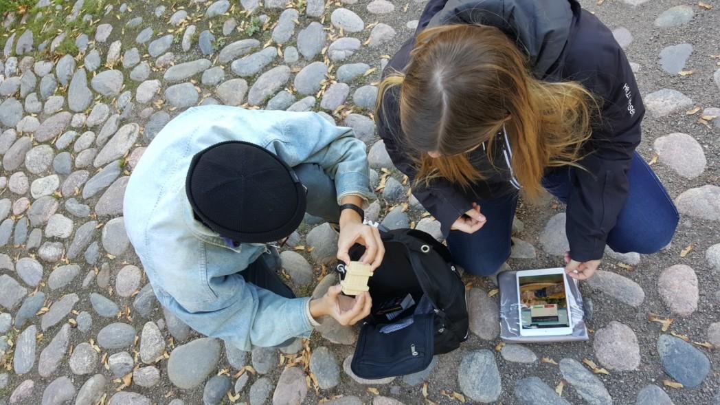 kaksi nuorta henkilöä tutkii esinettä mukulakivetyksellä, kuva on otettu yläsuunnasta. Maassa on älylaite.
